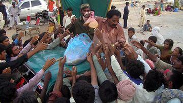 Ihmiset hakevat ruoka-avustuksia Larkanan telttakylässä Pakistanissa 24.8.2010. (EPA)
