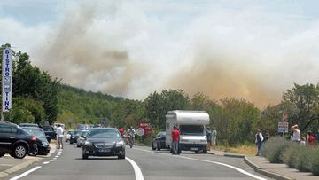 Tourist cars pass along the street as they escape the fire on background near Selce, a small town some 50 km south-east from Rijeka, at the Adriatic coast, 23 July 2012. Croatian authorities have evacuated all tourists from the village and camp because of the fire
