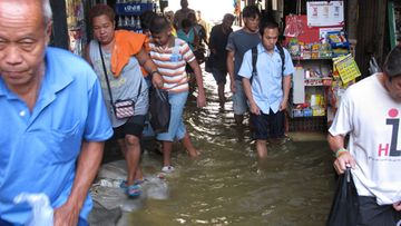 Thai residents walk through flooded streets as they come off boats on the Chao Phraya River in Bangkok, Thailand, 27 October 2011.