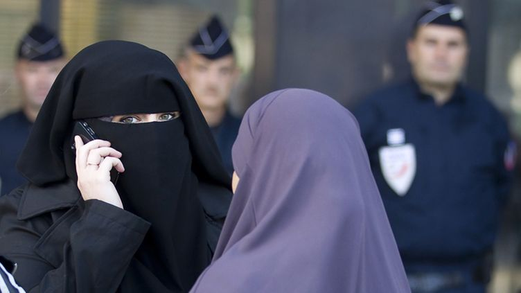 Women wearing niqabs in conversation as police officers stand watch in front of the courthouse in Meaux, near Paris, France, 22 September 2011