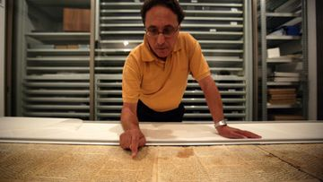 Dr. Adolfo Roitman, curator of the Dead Sea Scrolls and head of the Shrine of the Book points at the original Isaiah scroll found in Qumaran caves in the Judean Desert and dated around 120 BCE at the Israel Museum in Jerusalem, Israel, 26 September 2011.