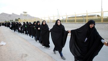 Iranian female students form a human chain, around the uranium conversion plant in Isfahan, to protest against the possible military threat by Israel in the city of Isfahan, central Iran, 15 November 2011.