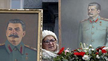 Georgialainen nainen ja Josef Stalinin kuvat Stalinin syntymäkaupungissa Gorissa joulukuussa 2008. EPA