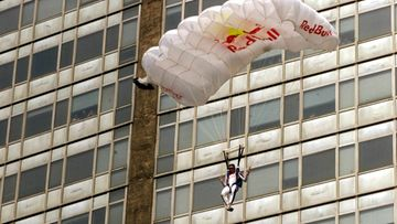 Austrian parachutist Felix Baumgartner plummets down as his chute opens after jumping from the top of the 137 metre high Pirelli skyscraper in the centre of Milan, Friday 30 July 1999.