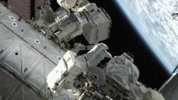 An image showing the Canada Arm 2 foot restraint holding Space Station resident and NASA astronauts Ron Garan (Top) working on the S2-Truss on the ISS with Mike Fossum (C) during the last space walk for an American Astronauts out side of the International Space Station