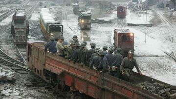 Rescuers come out of a pit in Longtan Colliery, where a flood killed 12 miners and left 16 missing, on October 6, 2005 in Guangan of Sichuan Province, southwest China.