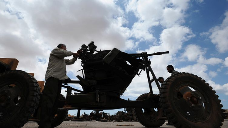 A picture made available the 16 of August 2011 shows a man belonging to the rebel fighters, preparing an anti-aircraft machine gun, at a rebel military base in Benghazi, Libya, 13 August 2011.