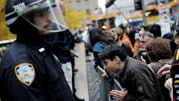 A man (R) prays while standing at the barricades around Zuccotti Park after the park was cleared of all tents and protestors in New York, New York, USA, 15 November 2011.