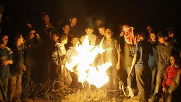 Palestinian gather around a fire next to a concrete wall, after it was broken down by a bulldozer, in the border between the Gaza Strip and Egypt in the town of Rafah Wednesday Jan. 4, 2006. Hundreds of Palestinians streamed unchecked into Egypt Wednesday and two Egyptian soldiers were killed after militants broke through a Gaza-Egypt border wall with stolen bulldozers. Two Egyptian soldiers were killed and 27 wounded by gunfire, Egyptian officials said, in the mayhem at the border. The armed Palestinians, linked to Abbas' own Fatah Party, stormed the border to reinforce their demand for the release of their leader, who is being held in the kidnapping of three Britons.