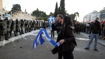 Protesters clash with riot police during a mass rally against the new memorandum outside the Greek Parliament in Athens, Greece, 12 February 2012