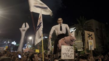 Demonstrators hold a puppet with the face of Israel's Prime Minister Benjamin Netanyahu sitting on a pig during a protest march against rising housing prices and social inequalities in Tel Aviv, on 06 August 2011.