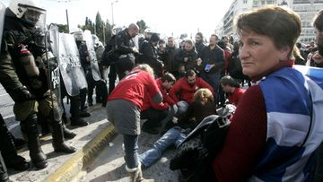 An injured protester is given first aid by medical staff during a rally in front of the Greek parliament in central Athens, Greece, 11 February 2012.