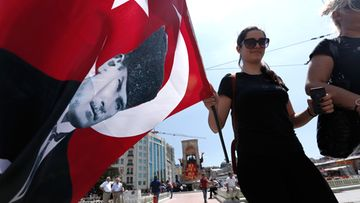 Activists walk with a Turkish flag after four days of demonstrations against the Turkish government in Istanbul, Turkey 03 June 2013.