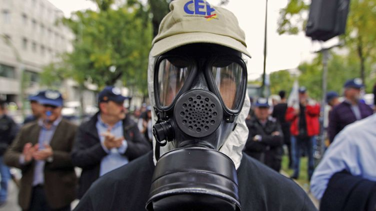 A protester wears a gas mask during a demonstration called by the Spanish Police Confederation, the Federal Police Union and the Police Professional Union that has gathered members of the National Police Force to protest against the government's cuts, at the Interior Ministry in Madrid, Spain, 27 October 2012.