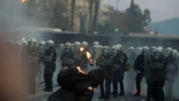Protesters clash with riot police during a mass rally against the new memorandum outside the Greek Parliament in Athens, Greece, 12 February 2012.