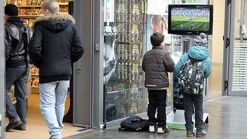Nuoret aiheuttavat harvoin isoja järjestyshäiriöitä kauppakeskuksissa. Nuoria koululaisia pelaamassa pelikonsolilla pelikaupan ulkopuolella Kampin kauppakeskuksessa Helsingissä tiistaina 2. huhtikuuta 2013.
