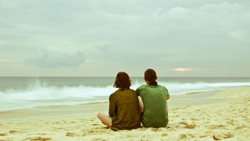 pari istuu rannalla