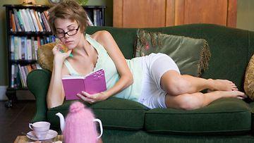 Nainen lukee kirjaa sohvalla