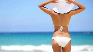 nainen seisoo rannalla