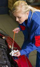 Nainen vaihtaa öljyjä autoon