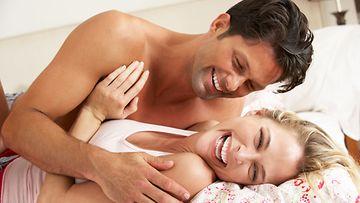 Hymyilevä pariskunta sängyssä