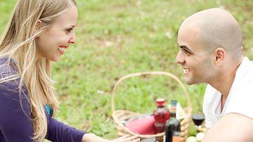 Hymyilevä pariskunta nurmikolla