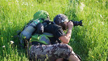 Luontokuvaaja kuvaa pellolla