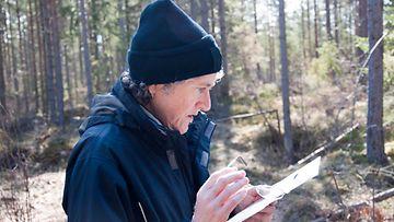 Suunnistaja katsoo karttaa metsässä
