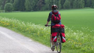 Nainen pyöräilee maaseudulla