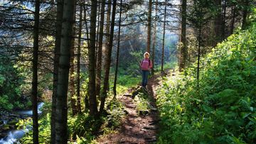 Nainen seisoo metsäpolulla