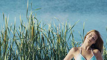 Nainen bikineissä meren äärellä