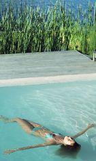 Nainen kelluu uima-altaassa