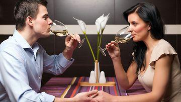 Mies ja nainen juovat viiniä ravintolassa