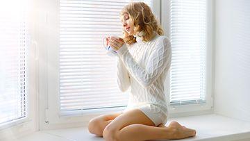 Nainen juo kahvia ikkunalla