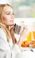 Nainen juo kahvia kylpytakissa