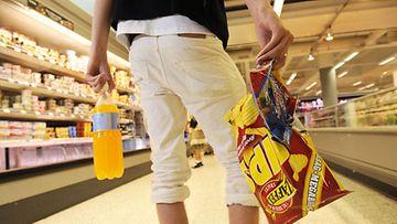 Nuori ostaa perunalastuja, karkkeja ja virvoitusjuomaa.