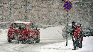 Auto ja ihmisiä lumisateessa Unioninkadulla Helsingissä 20. tammikuuta 2012.