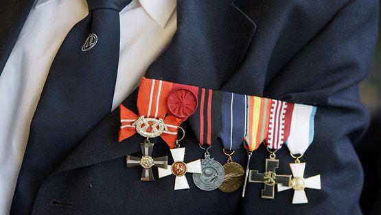 Suomalaisia sotaveteraaneja Kuusikodissa Nuuksiossa viettämässä Puolustusvoimain lippujuhlan päivää. Miehen rinnassa rivi kunniamerkkejä.