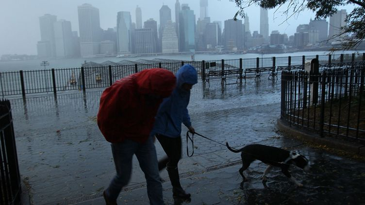 NEW YORK, NY - OCTOBER 30: A couple walks in the rain as a darkened Manhattan is viewed after much of the city lost electricity due to the affects of Hurricane Sandy on October 30, 2012 in New York, United States. At least 15 people were reported killed in the United States by Sandy as millions of people in the eastern United States have awoken to widespread power outages, flooded homes and downed trees. New York City was his especially hard with wide spread power outages and significant flooding in parts of the city. (Photo by Spencer Platt/Getty Images)