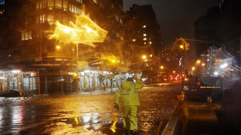 (NEW YORK, NY - OCTOBER 29: A Con Edison worker walks through the flood waters on the corner of 33th Street and 1st Street in front of NYU Langone Medical Center in Manhattan during rains from Hurricane Sandy on October 29, 2012 in New York City. Hurricane Sandy, which threatens 50 million people in the eastern third of the U.S., is expected to bring days of rain, high winds and possibly heavy snow. New York Governor Andrew Cuomo announced the closure of all New York City bus, subway and commuter rail services as of Sunday evening. (Photo by Michael Heiman/Getty Images) )