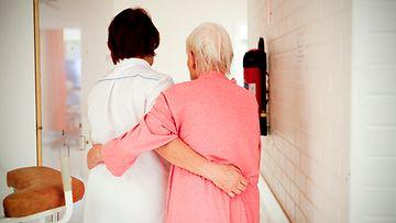 Lääkäri taluttaa vanhusta sairaalassa.