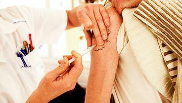 Sairaanhoitaja antaa rokotteen.