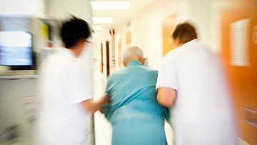 Vanhusta talutetaan sairaalan käytävällä.