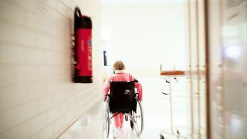 Potilas pyörätuolissa sairaalan käytävällä.