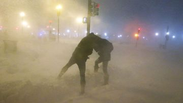 People shield themselves from the blowing snow as a blizzard arrives in the Back Bay neighborhood on February 8, 2013 in Boston, Massachusetts.