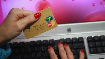 Nainen ostaa luottokortilla internetistä. (Lehtikuva)