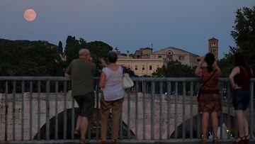 Ihmiset ihailemassa superkuuta Roomassa 10. elokuuta 2014.