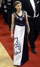 Suomen partiolaisten puheenjohtaja Heidi Jokisen  iltapuvun helmaa koristi valtava Suomen partiolaisten liljan mallinen logo.