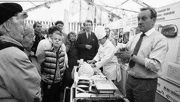 """19901005 HELSINKI: Harri Holkeri paistamassa ja syömässä silakkaa saaristokuntien PR-kampanjateltassa Kauppatorilla, kampanja """"Hyvän elämän saaristo""""."""