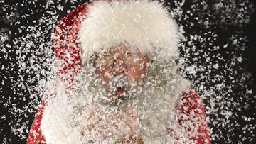 Joulupukki puhaltaa lunta. Lehtikuva